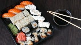 Large sushi sets with lots of sushi, roll, maki, nigiri, gunkan. Stylish sushi sets on black wooden table next to soy. Large sushi sets with lots of sushi, roll stock video footage