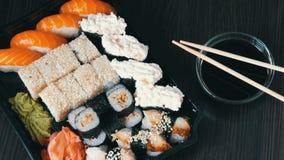Large sushi sets with lots of sushi, roll, maki, nigiri, gunkan. Stylish sushi sets on black wooden table next to soy. Large sushi sets with lots of sushi, roll stock video