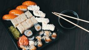 Large sushi sets with lots of sushi, roll, maki, nigiri, gunkan. Stylish sushi sets on black wooden table next to soy. Large sushi sets with lots of sushi, roll stock footage