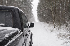 Large SUV driving on a snow-covered road in the forest Stock Photos