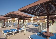 Swimming pool and sun loungers at a luxury tropical hotel resort Stock Images