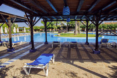 Large swimming pool with sun loungers, umbrellas and a gazebo Royalty Free Stock Photos