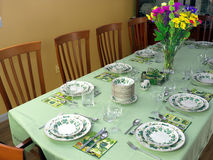 Large table set for fancy dinner. Table for 12 people with light green tablecloth and beautiful porcelain service waiting for the guests to arrive. Colorful Royalty Free Stock Photo