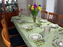 Large table set for fancy dinner. Table for 12 people with light green tablecloth and beautiful porcelain service waiting for the guests to arrive. Colorful Stock Images