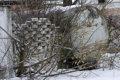 A large tank for collecting milk near a stone fence. In the abandoned and destroyed factory on the background of white snow in winter. Ruin and vandalism royalty free stock images