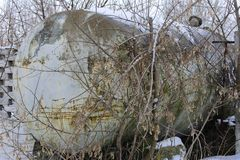 A large tank for collecting milk near a stone fence. In the abandoned and destroyed factory on the background of white snow in winter. Ruin and vandalism royalty free stock photo