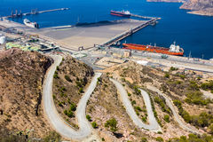 Large tankers in a port next to a mountain royalty free stock photos