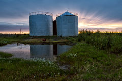 Large tanks at sunset sky background. Royalty Free Stock Photo