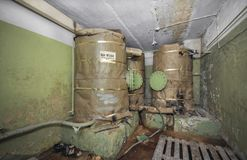 Large tanks with a supply of drinking water for autonomous existence in the underground shelter. An abandoned old shelter with a s stock images
