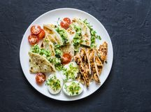 Large tapas plate - grilled, chicken, avocado cream cheese quesadilla, boiled eggs, vegetables - tasty snack on a dark background. Top stock image