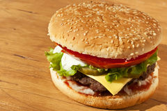Large Tasty Cheeseburger on Wooden table Royalty Free Stock Photo