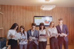 Large team of people is working at one table for laptops, tablets and papers, on the background a large TV set on a wooden wall royalty free stock image