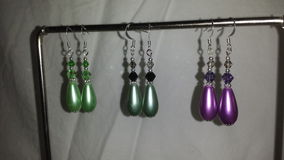 Large teardrop pearl earrings in lime green, purple or sage green. Royalty Free Stock Photos
