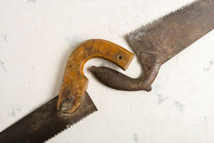 Large teeth of an old saw on wood. Sharp and uneven edges. Rusted surface. Light stone background. Copy space Stock Image