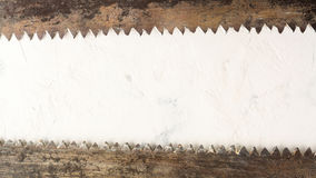 Large teeth of an old saw on wood. Sharp and uneven edges. Rusted surface. Light stone background. Copy space Royalty Free Stock Images