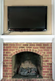Large television over fireplace. Large television hung over top of a gas fire place Stock Photos