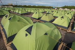 A large tent camp, located on the sand. Many green tents install. A large number of tents on a sandy beach, lined up strictly in a row royalty free stock photos