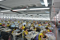 Large textile factory with valuable workers. Diligent workers in a textile factory in their workplace for sewing machines royalty free stock image