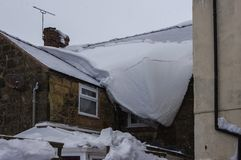 Large thick sheet of icy snow hanging off roof. Royalty Free Stock Photography
