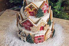 Large tiered Christmas cake decorated with gingerbread cookies and a house on top. Tree and garlands in the background. Royalty Free Stock Photo