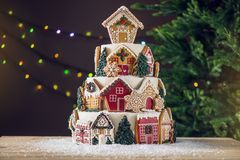 Large tiered Christmas cake decorated with gingerbread cookies and a house on top. Tree and garlands in the background. Stock Photos