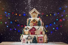 Free Large Tiered Christmas Cake Decorated With Gingerbread Cookies And A House On Top. Tree And Garlands In The Background. Stock Photo - 104902330