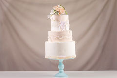 A large tiered wedding cake in the form of dress with lace decorated with pink roses on top of the table. The concept of festive desserts Royalty Free Stock Photography