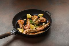 Prawns shrimps with garlic, lemon, spices and italian parsley garnish in a black pan on a dark stone background. Large tigers prawns shrimps head on with garlic royalty free stock photography