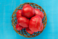 Large tomatoes in a wooden basket on a blue background. Tomatoes background. Royalty Free Stock Photos