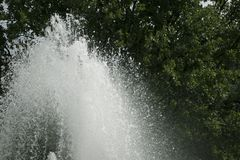 Large top of fountain jet gushing upwards. Against green foliage royalty free stock photography