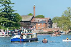Large tour boat approaches bridge surrounded by flotilla of smaller boats in the uk. May 6th 2018 bank holiday with crowds of people enjoying the river avon in Royalty Free Stock Photo