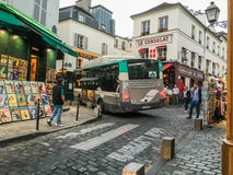 Large tourist bus winds through narrow Montmartre street Royalty Free Stock Image