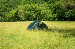 A large tourist tent stands on a meadow on a warm summer day. In nature, replaces the house with man Royalty Free Stock Photography