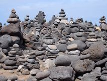 Large towers of stacked pebbles on a beach with blue sky Stock Image