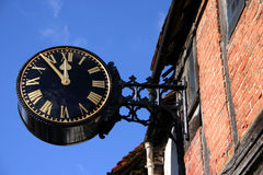 Large Town Clock. Large black town clock attached to brick and timber building against blue sky Royalty Free Stock Images