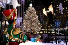 A Large toy nutcracker drummer statue and the holiday lights in Rockefeller Center stock photo