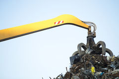 Large tracked excavator working a steel pile. At a metal recycle yard Royalty Free Stock Images