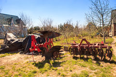 large tractor-drawn plough seeder in country garden in spring Stock Images