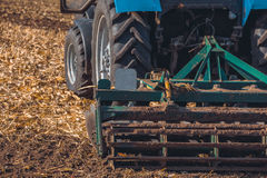 Large tractor pulling a plow and plow the field, remove the remnants of the previously beveled corn. Stock Photography