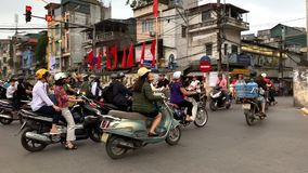 Large traffic of motorbikes on busy crossroad in Hanoi