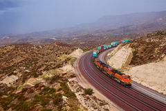 Large train passing through the curve. Large locomotives, carriages pulled behind a lot of goods Stock Photos