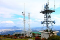 The tower is located on a high mountain with white clouds. stock photo