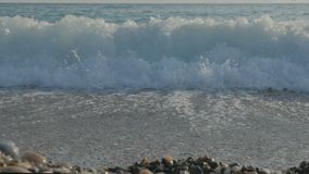 Large transparent waves with foam. Sea pebble beach with colorful stones. Slow motion stock footage