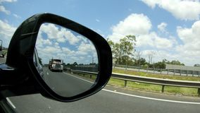 Large truck on highway view from car side mirror stock footage