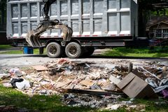 Large truck picking up trash and debris outside of Houston neighborhood royalty free stock image