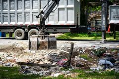 Large truck picking up trash and debris outside of Houston neighborhood royalty free stock photo