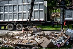 Large truck picking up trash and debris outside of Houston neighborhood stock image