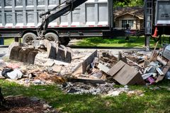 Large truck picking up trash and debris outside of Houston neighborhood royalty free stock images