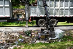 Large truck picking up trash and debris outside of Houston neighborhood stock photo