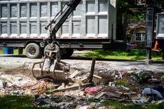 Large truck picking up trash and debris outside of Houston neighborhood royalty free stock image